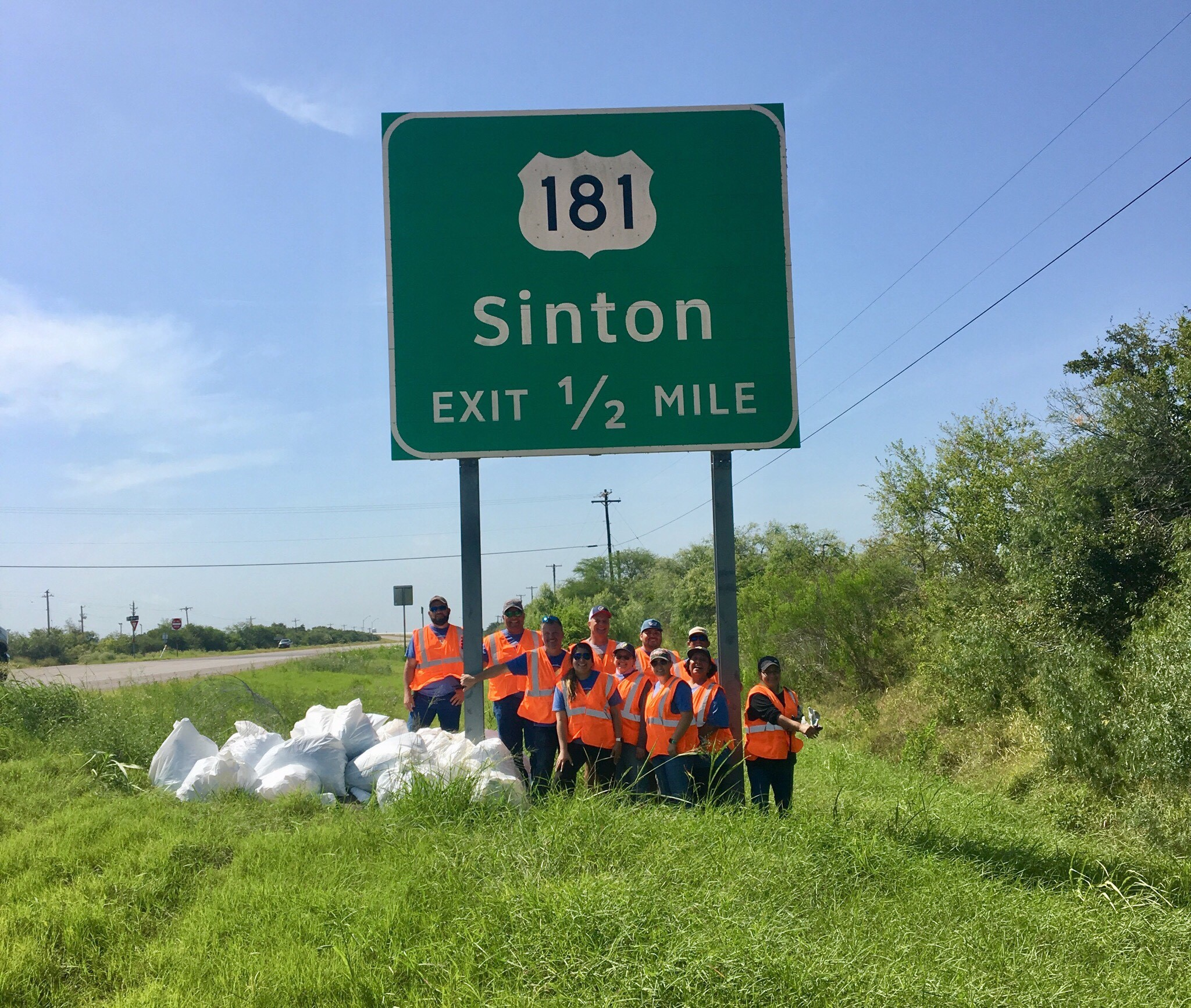 SPEC Employees posing next to sign and trash collected at Adopt-A-Highway